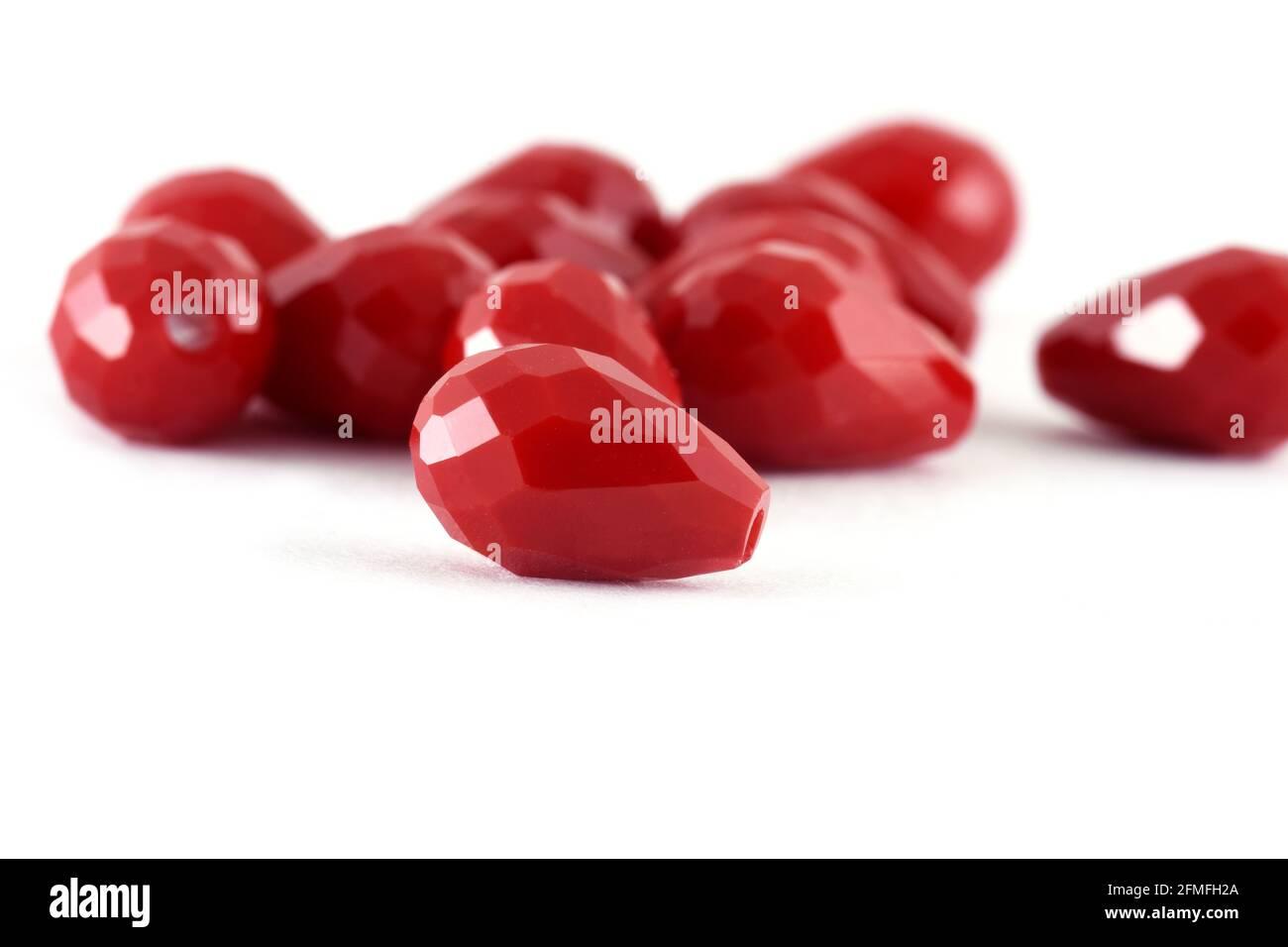 Forma de gota Cuentas rojas esparcidas sobre fondo blanco. Fondo o textura de beads.Close para arriba, usado en la ropa de la manera del acabado. Haga collar de la perla o stri Foto de stock