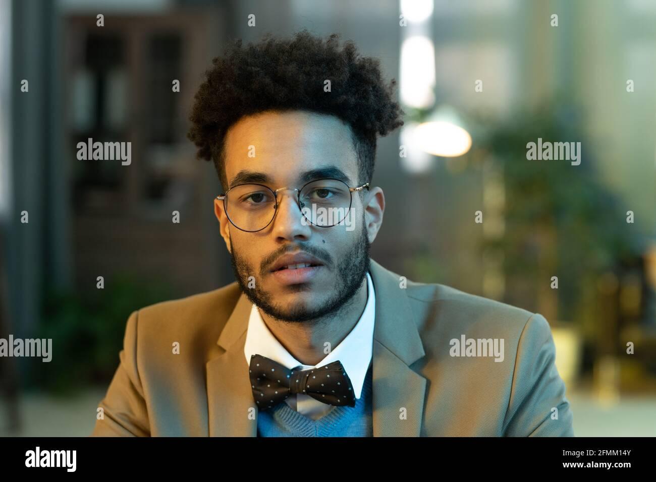 Retrato de un hombre joven con pelo afro rizado gafas de forma redonda y pajarita sentado en la oficina Foto de stock
