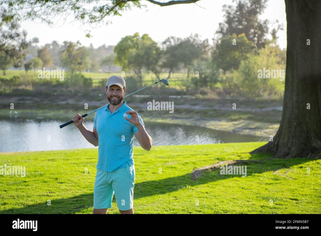 Retrato del golfista feliz del smilin que golpea tiro del golf con el club en el campo. Foto de stock