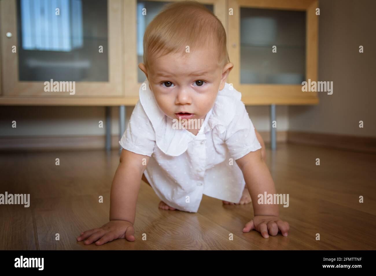 Hermoso bebé de 1-2 años arrastrándose en la sala de estar en casa. Foto de stock