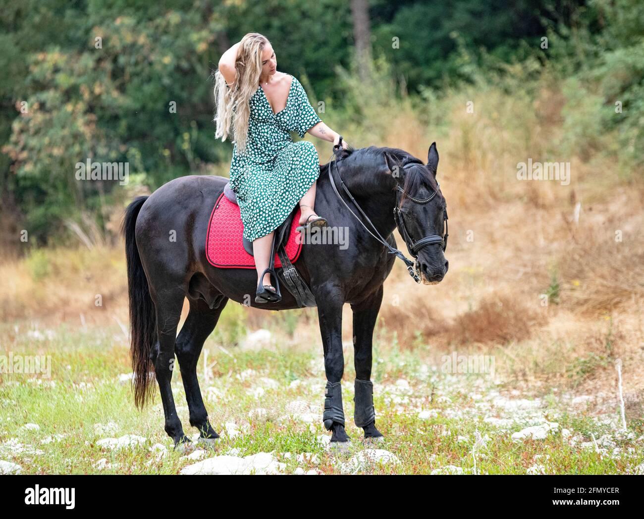 la chica de montar a caballo está caminando con su caballo negro Foto de stock