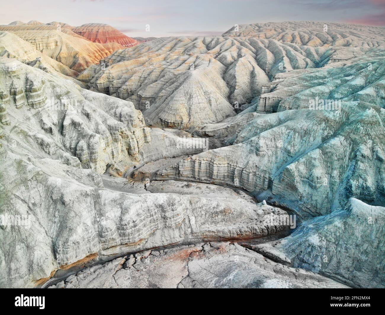 Aviones teledirigidos Paisaje de Bizarre en capas de rojo, azul y blanco montañas del desierto con cañón en el hermoso parque nacional Altyn Emel en Kazakhstan Foto de stock