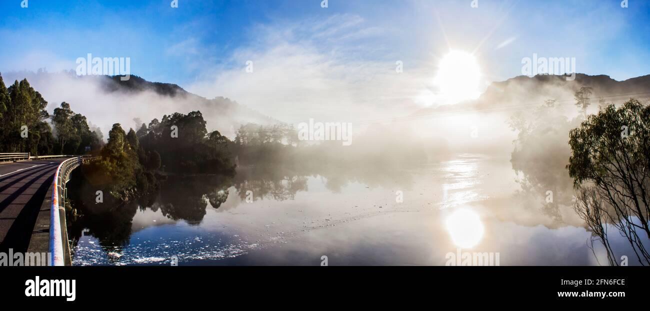 Paisaje panorámico panorámico de neblina a primera hora de la mañana en el lago Rosebery, en Tullah Tasmania, Australia, con el sol reventando sobre los picos de la montaña y la ref Foto de stock