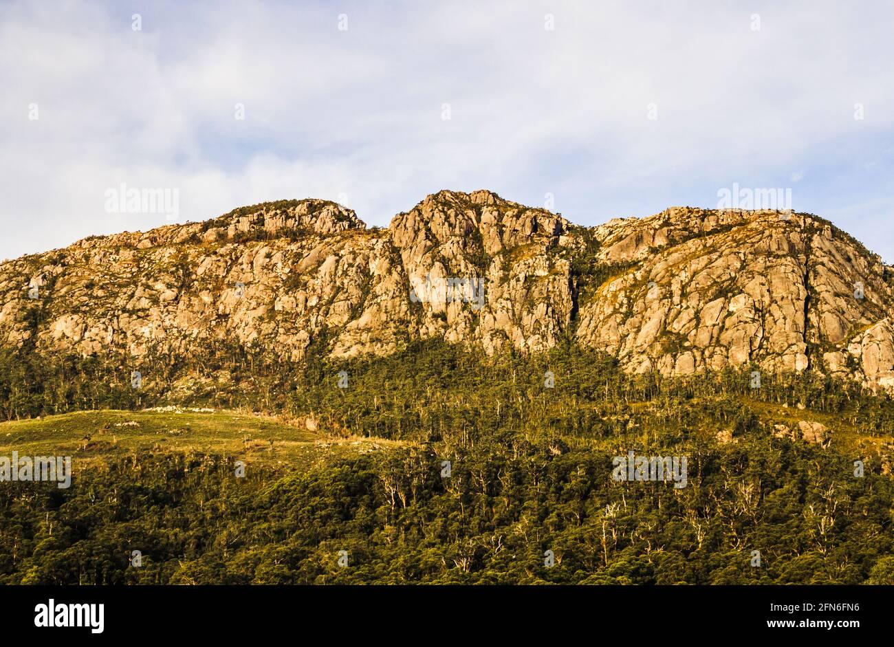 Escarpado paisaje de montaña Tullah del Monte Farrell entre la vegetación verde del bosque y la cobertura de nubes blancas en el oeste de Tasmania, Australia Foto de stock