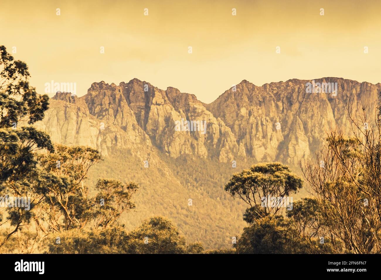 Paisaje de campo vintage de una cordillera dura pero impresionante capturada de una abertura del bosque. Monte Read, Costa Salvaje Oeste de Tasmania Foto de stock