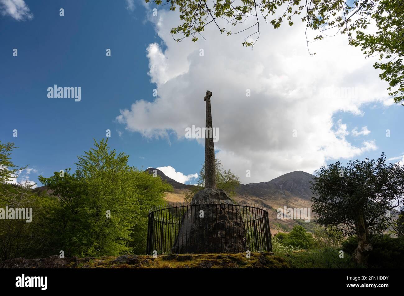 Glencoe Massacre Memorial cruce en Glencoe pueblo, Tierras Altas escocesas en un día soleado con cielo azul y nubes. Foto de stock