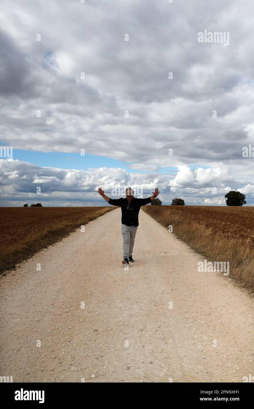 Hombre feliz caminando solo en la carretera de campo recta. Cielo nublado. Francia. Foto de stock
