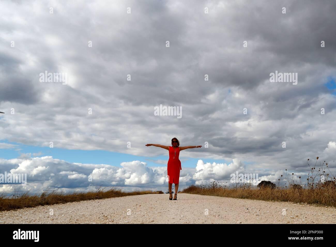 Mujer caminando sola por carretera recta. Cielo nublado. Francia. Foto de stock