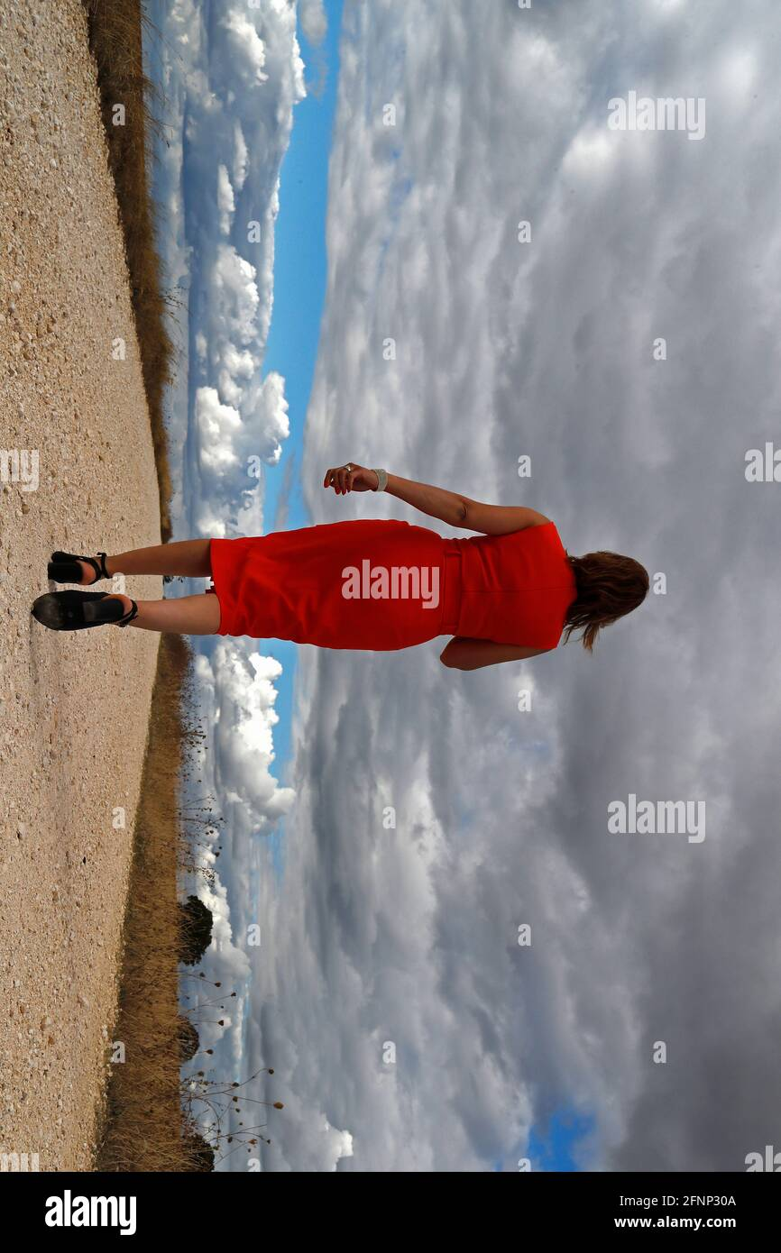 Vista trasera de una mujer caminando sola en la carretera de campo recta. Cielo nublado. Francia. Foto de stock