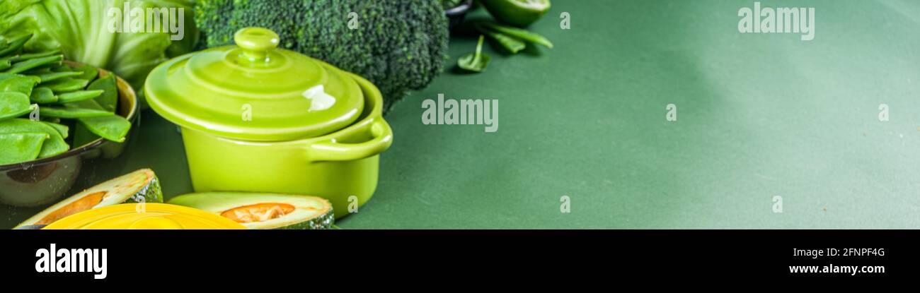 Varios ingredientes vegetales de primavera verde orgánico con vacio coloridas ollas de cocina portioned en mesa de cocina verde oscuro, vista superior. Dieta sopa saludable Foto de stock