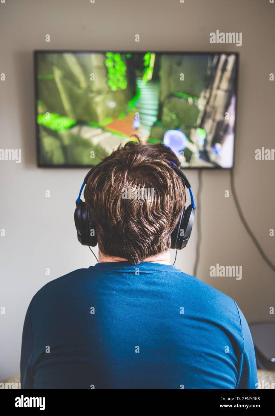 Vista trasera de un adolescente mirando la televisión mientras estaba jugar a videojuegos y usar micrófono y auriculares Foto de stock