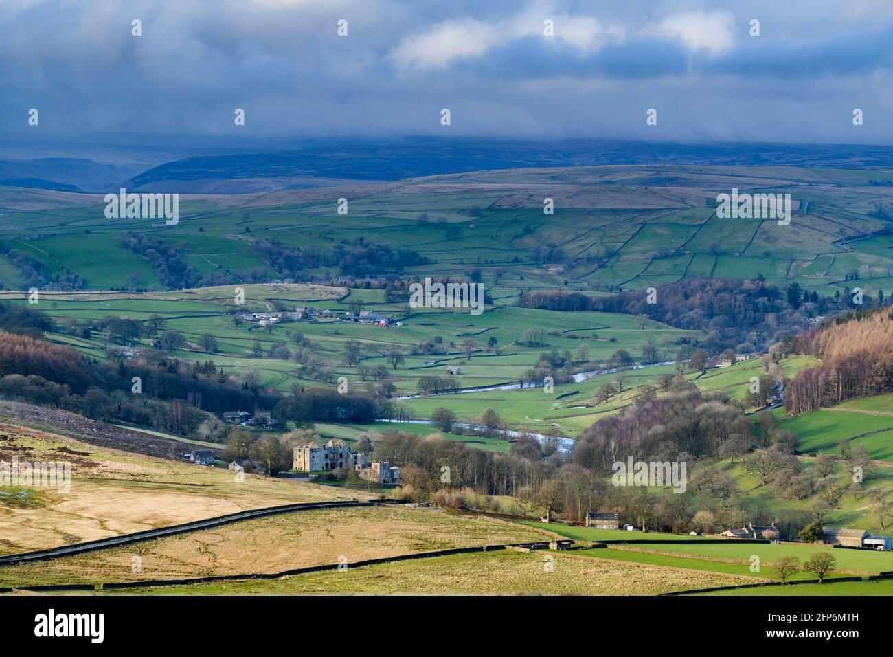 Vista rural escénica de Wharfedale (amplio valle verde, colinas ondulantes, altas colinas y páramos, ruinas iluminadas por el sol de la Torre Barden) - Yorkshire Dales England, Reino Unido Foto de stock