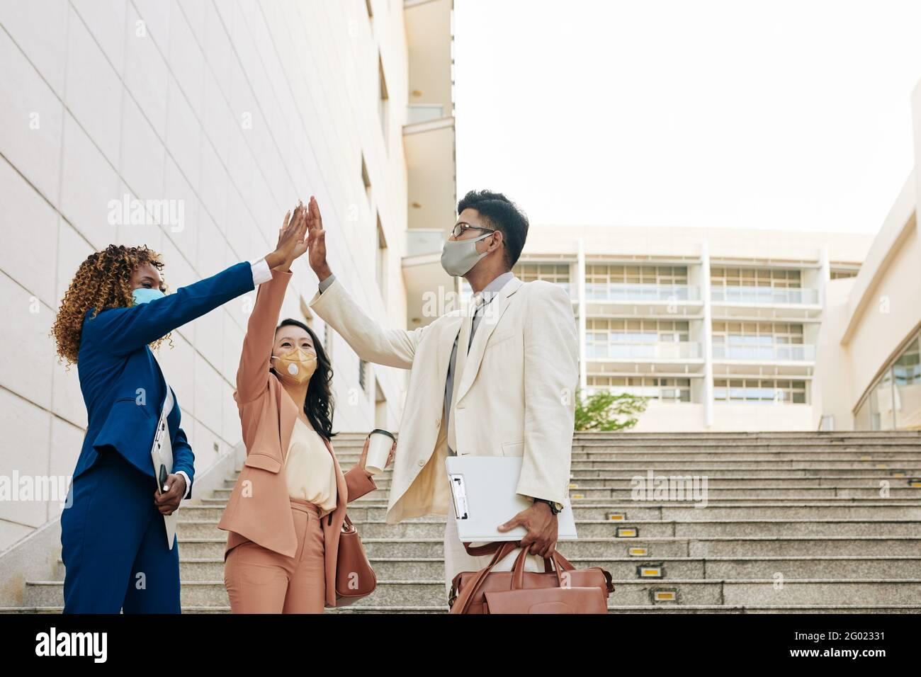 Grupo de gente feliz de negocios emocionados en máscaras médicas de pie al aire libre y dándose unos a otros cinco altos después de terminar el trabajo en proyecto grande Foto de stock