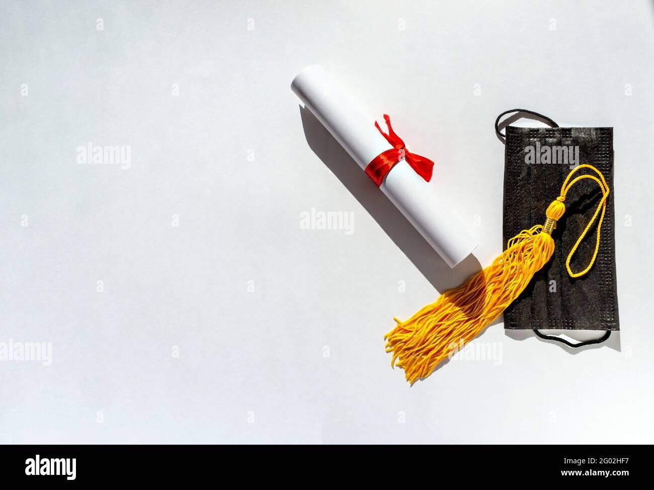 Borla amarilla de la tapa de graduación, papel de rollo atado con cinta roja con lazo, diploma y máscara de protección de la cara negra sobre fondo blanco, nueva realidad Foto de stock