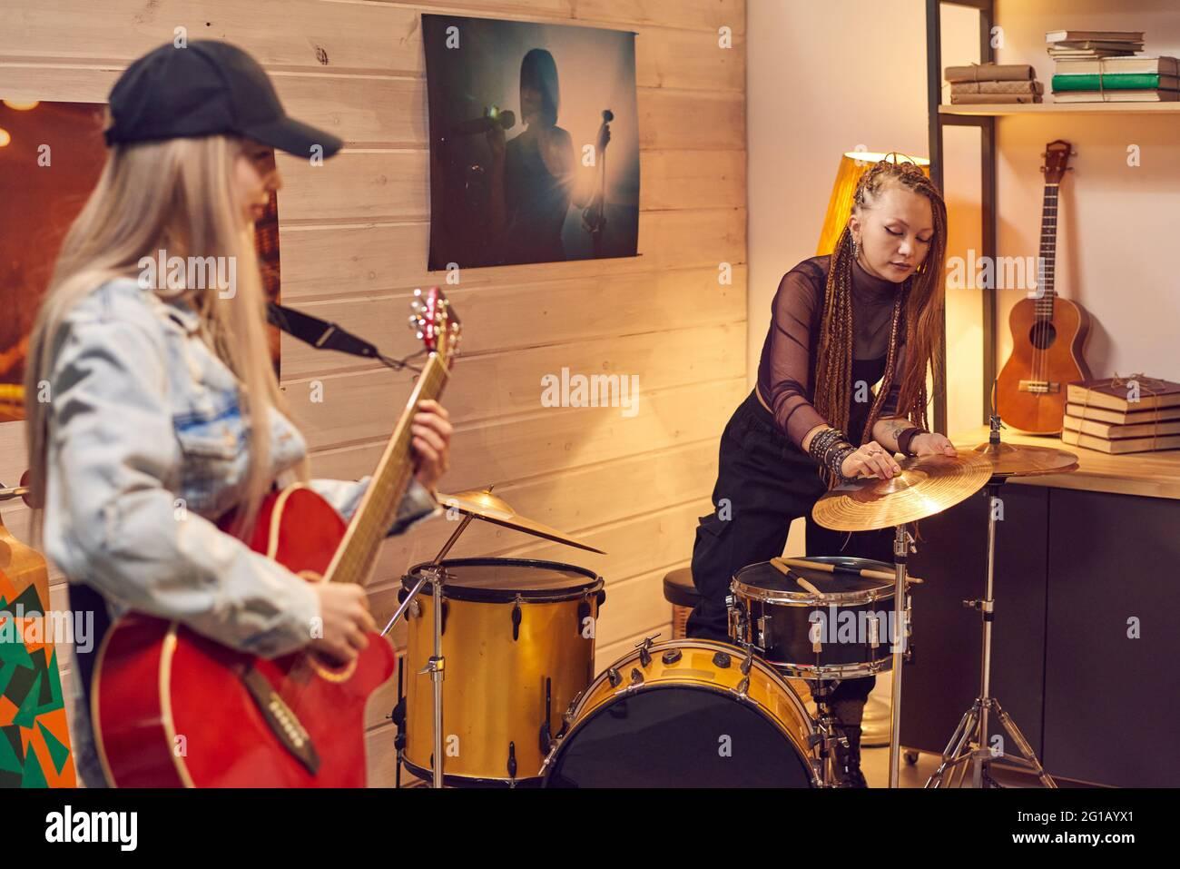 Niñas con instrumentos musicales preparándose para la grabación de música en el estudio Foto de stock