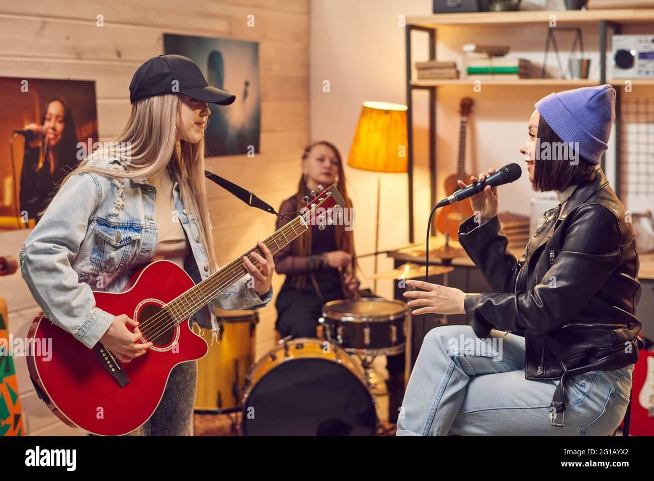 Chica con micrófono cantando entre sus amigos con instrumentos musicales Foto de stock