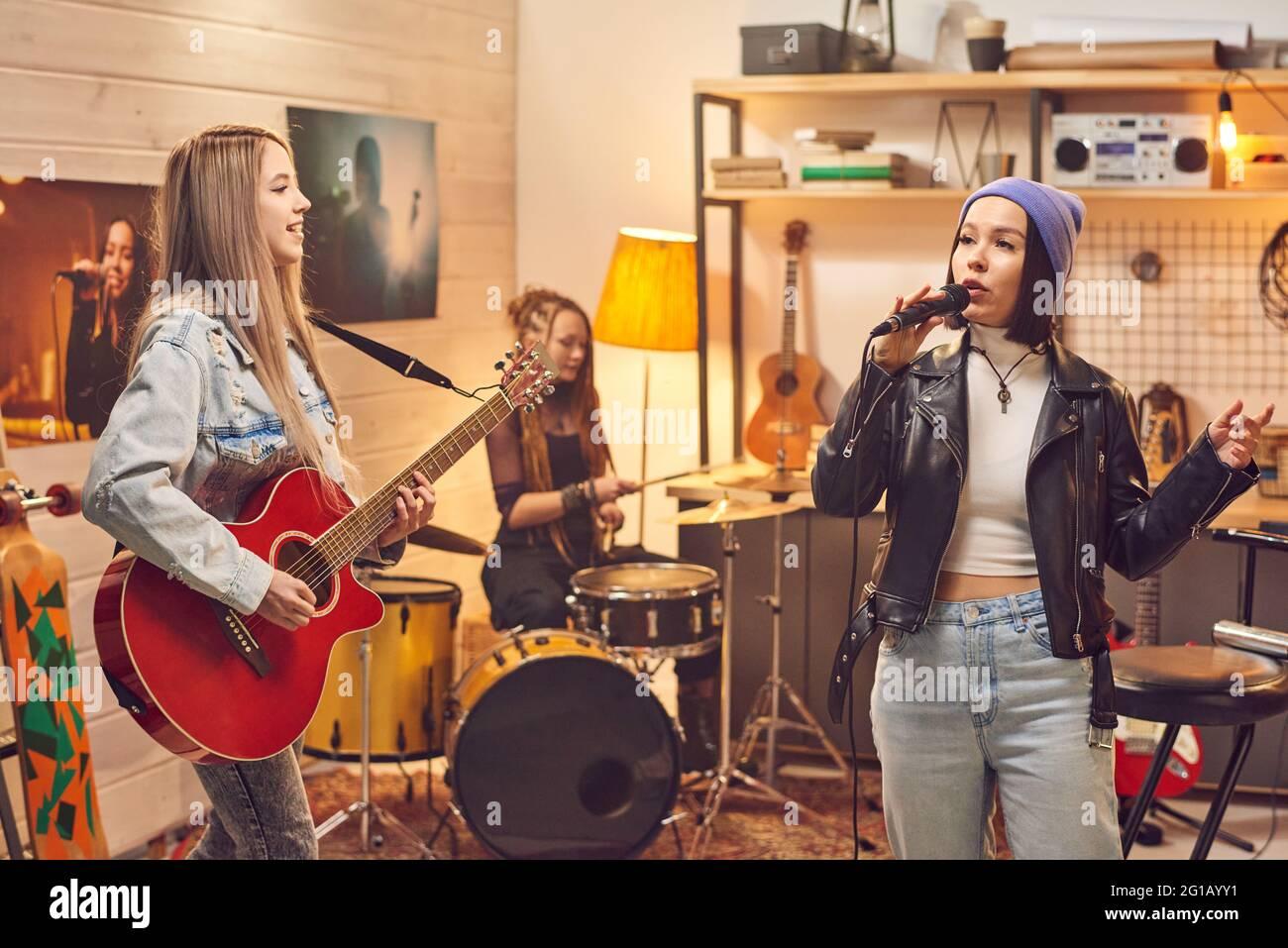Banda femenina compuesta por tres chicas grabando canciones en el estudio Foto de stock