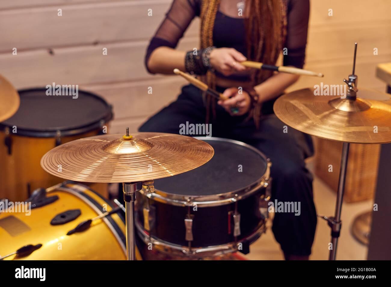 Juego de batería y joven mujer con muslos sentados cerca Foto de stock