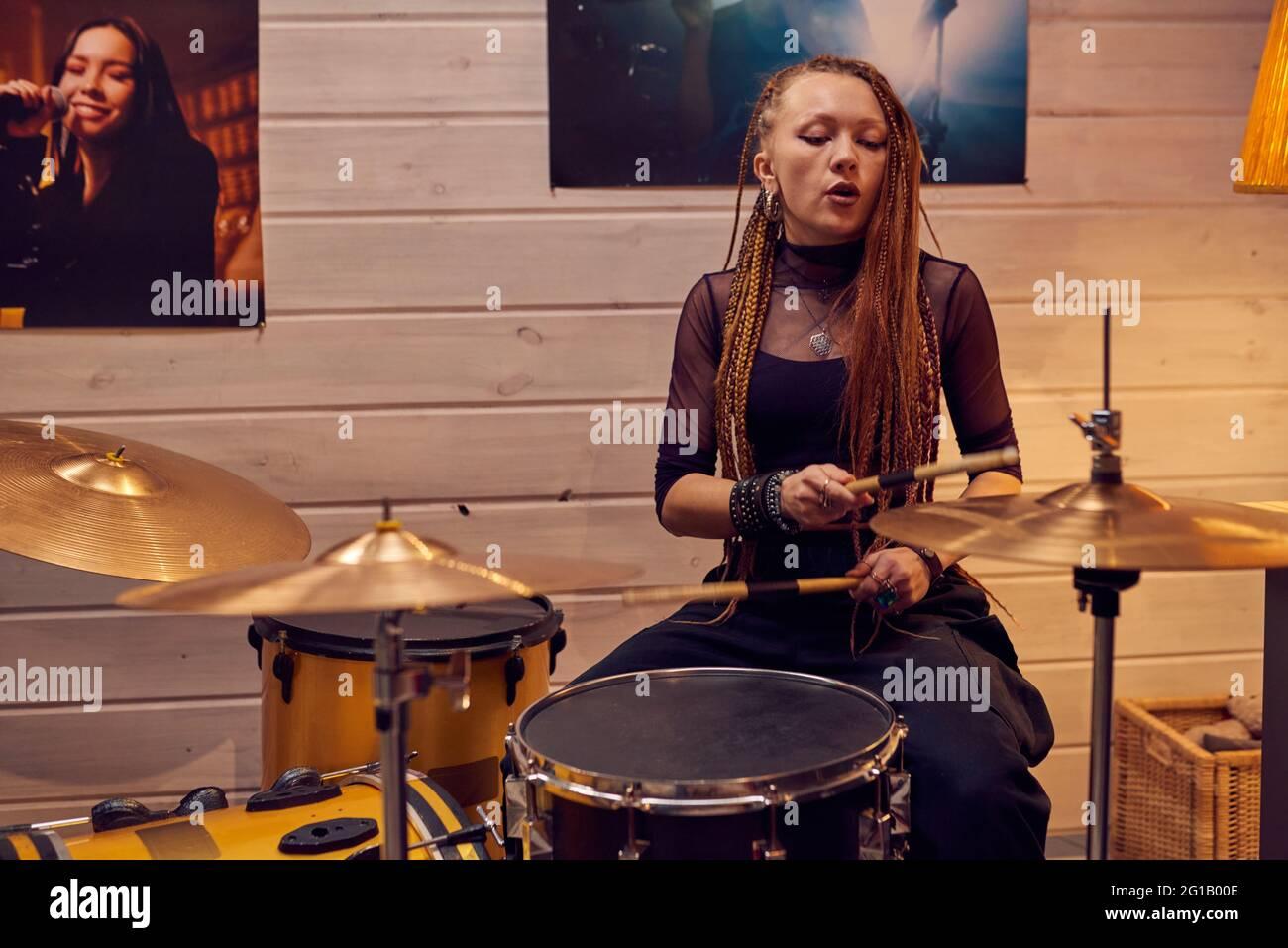 Chica sentada junto al tambor mientras grababa música en un estudio moderno Foto de stock