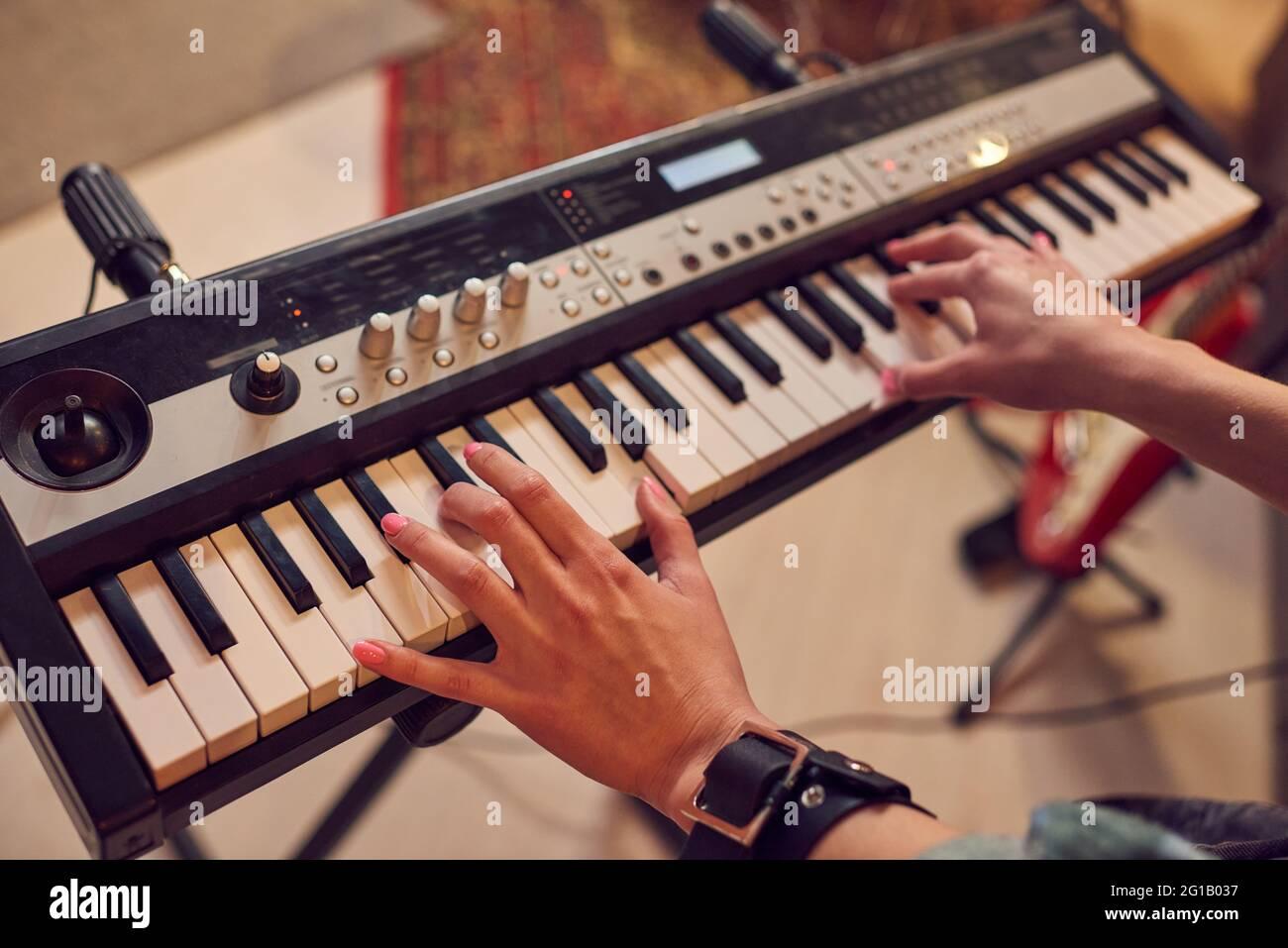Joven tocando sintetizador en estudio de discos de sonido Foto de stock