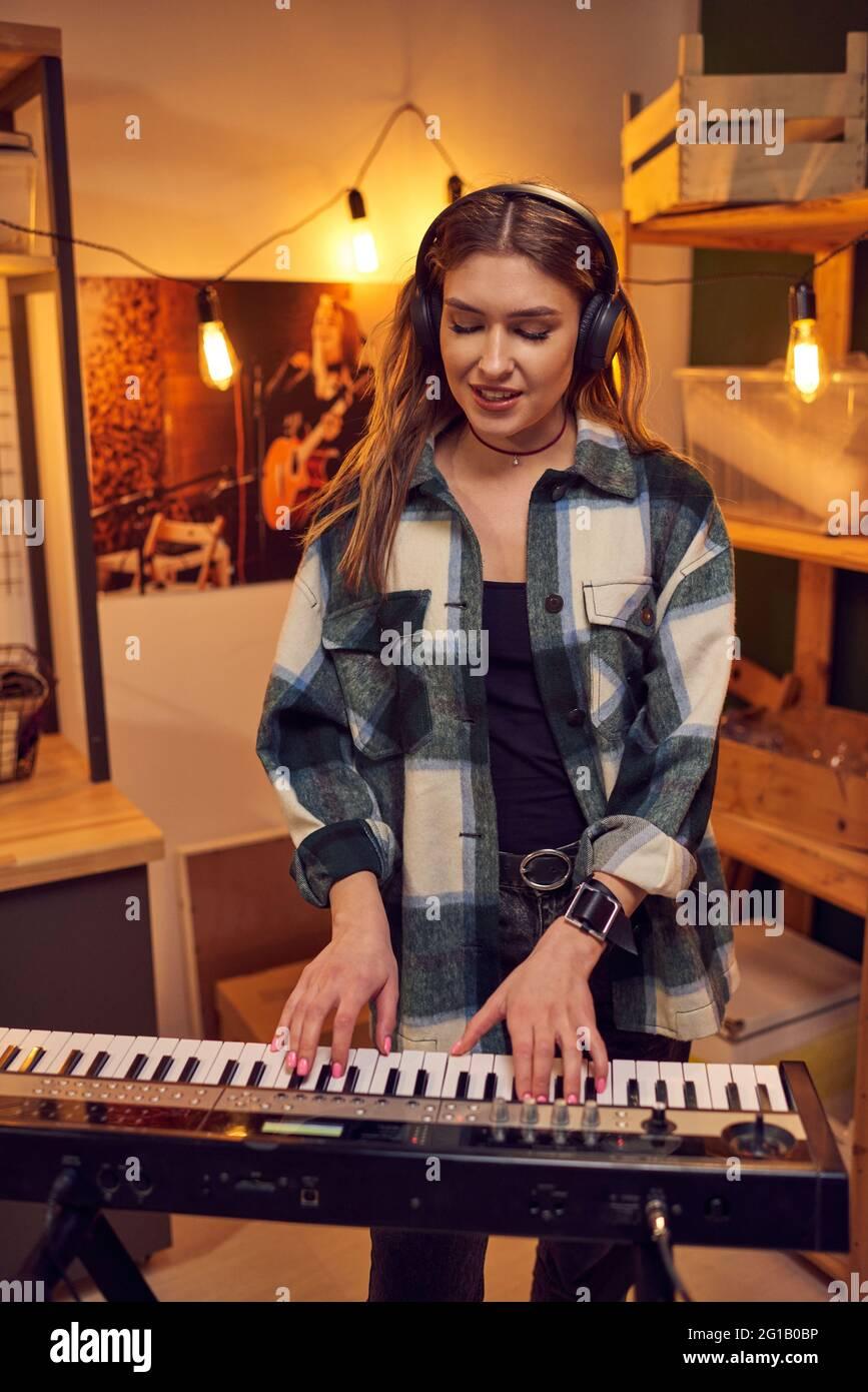 Mujer rubia tocando sintetizador y cantando en estudio Foto de stock