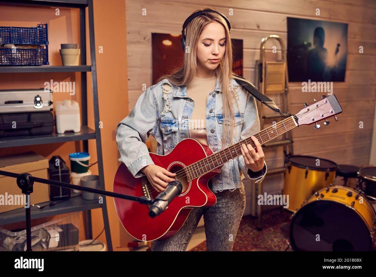 Chica con pelo rubio largo tocando la guitarra eléctrica en el estudio Foto de stock