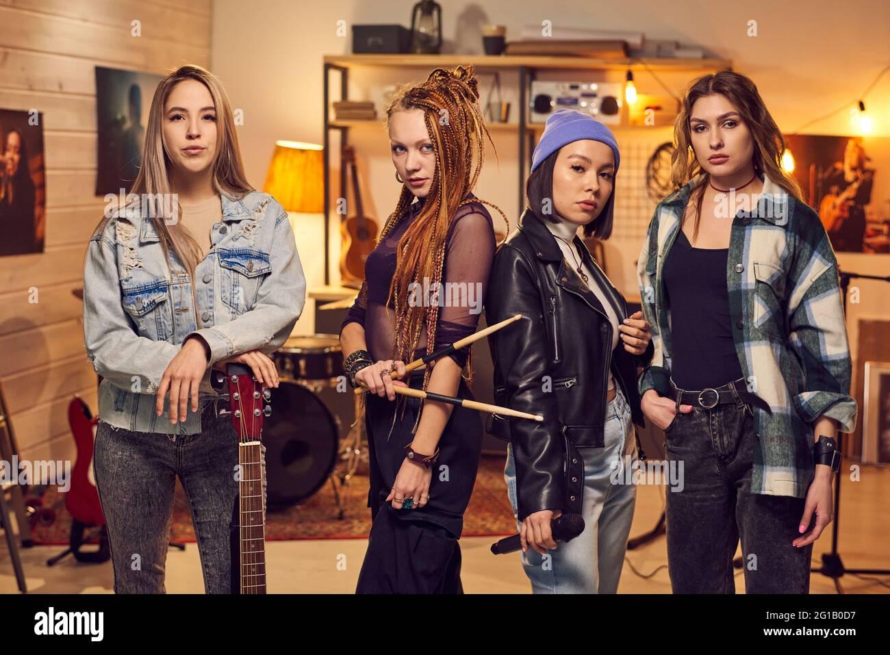 Banda de chicas que consta de cuatro mujeres de pie en fila en el estudio Foto de stock