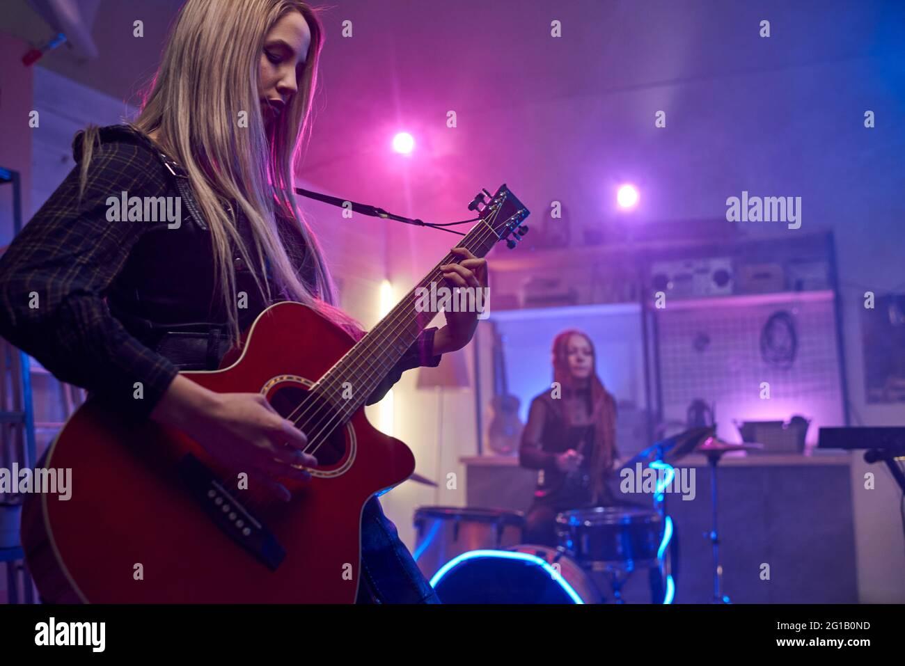 Una mujer rubia tocando guitarra eléctrica durante la actuación en escena Foto de stock