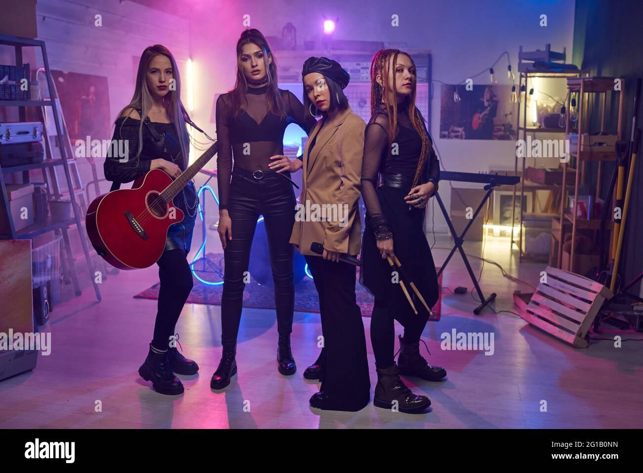 Grupo de mujeres jóvenes con instrumentos musicales de pie en estudio Foto de stock