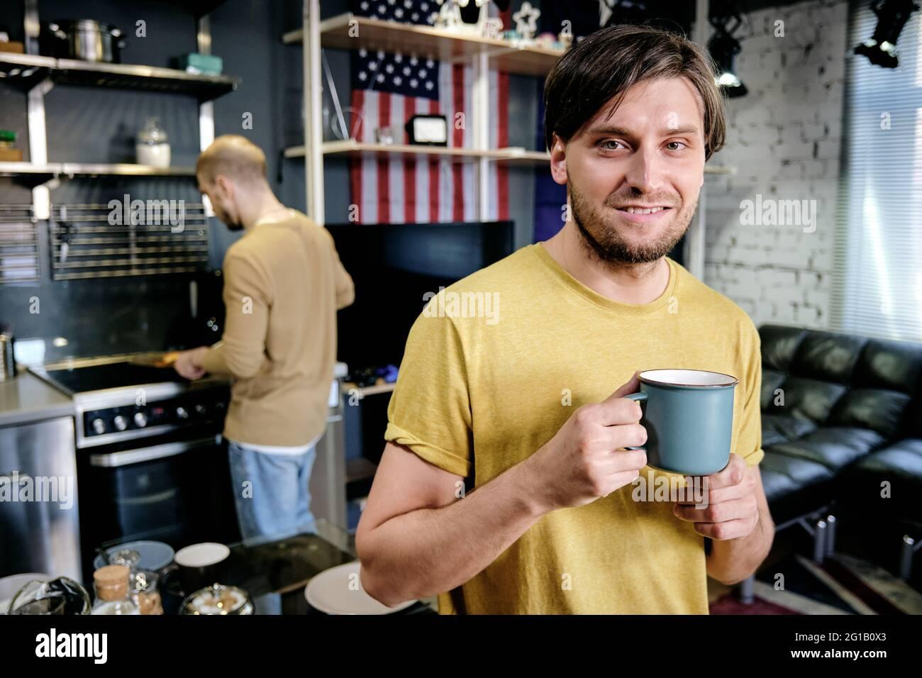 Un hombre sonriente bebiendo contra un hombre que cocina el desayuno en la cocina Foto de stock