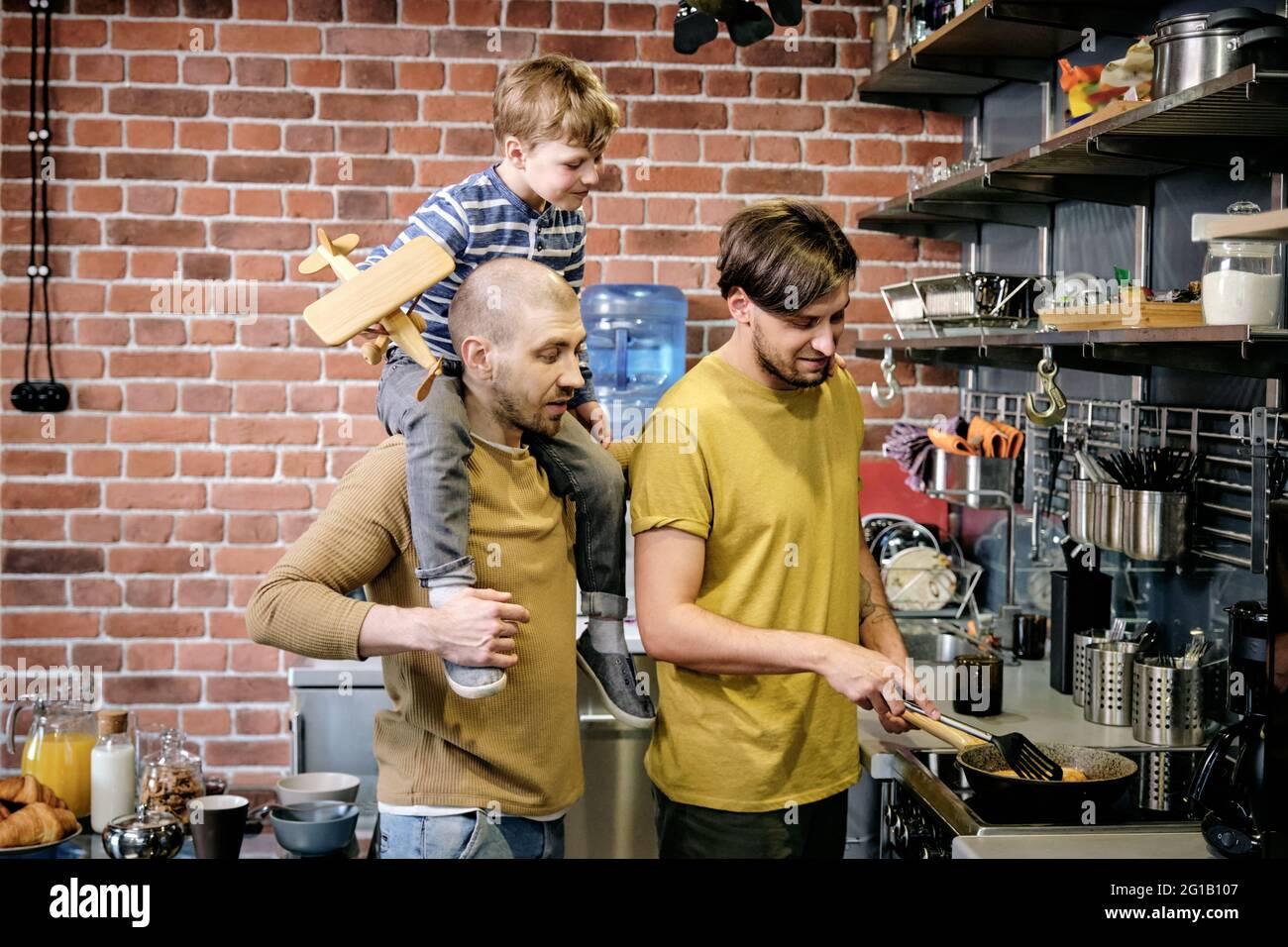 Dos hombres gays felices y un niño pequeño cocinando en el ambiente de la cocina Foto de stock