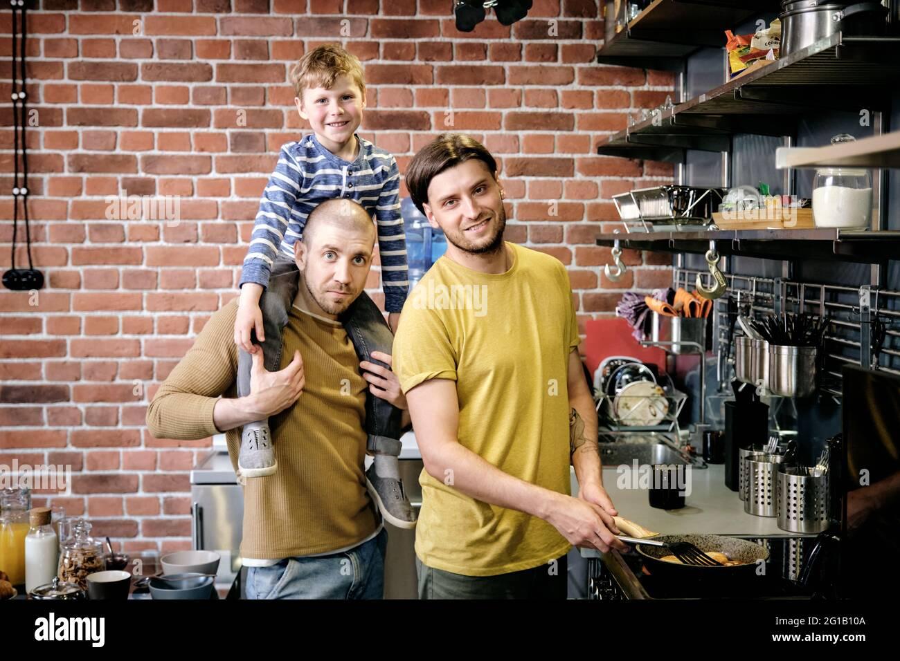 Dos varones jóvenes y su lindo hijo cocinando en la cocina Foto de stock