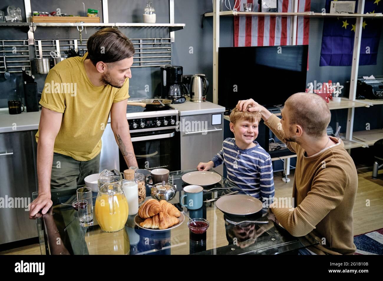Feliz niño pequeño y dos hombres jóvenes hablando por mesa en la cocina Foto de stock
