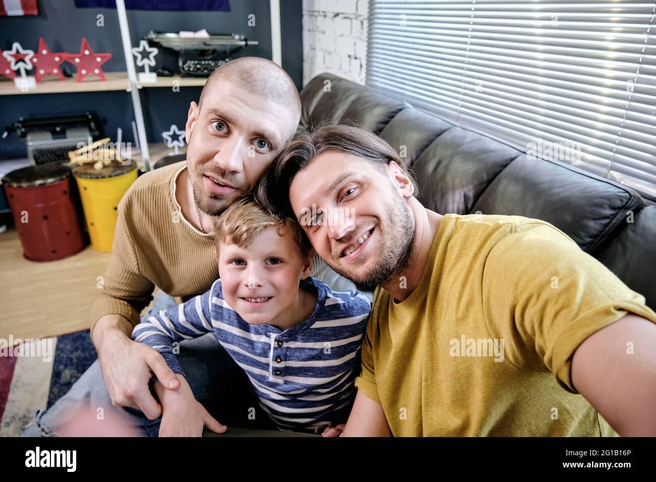 Dos hombres amorosos que hacen selfie con niño pequeño lindo en el ambiente casero Foto de stock
