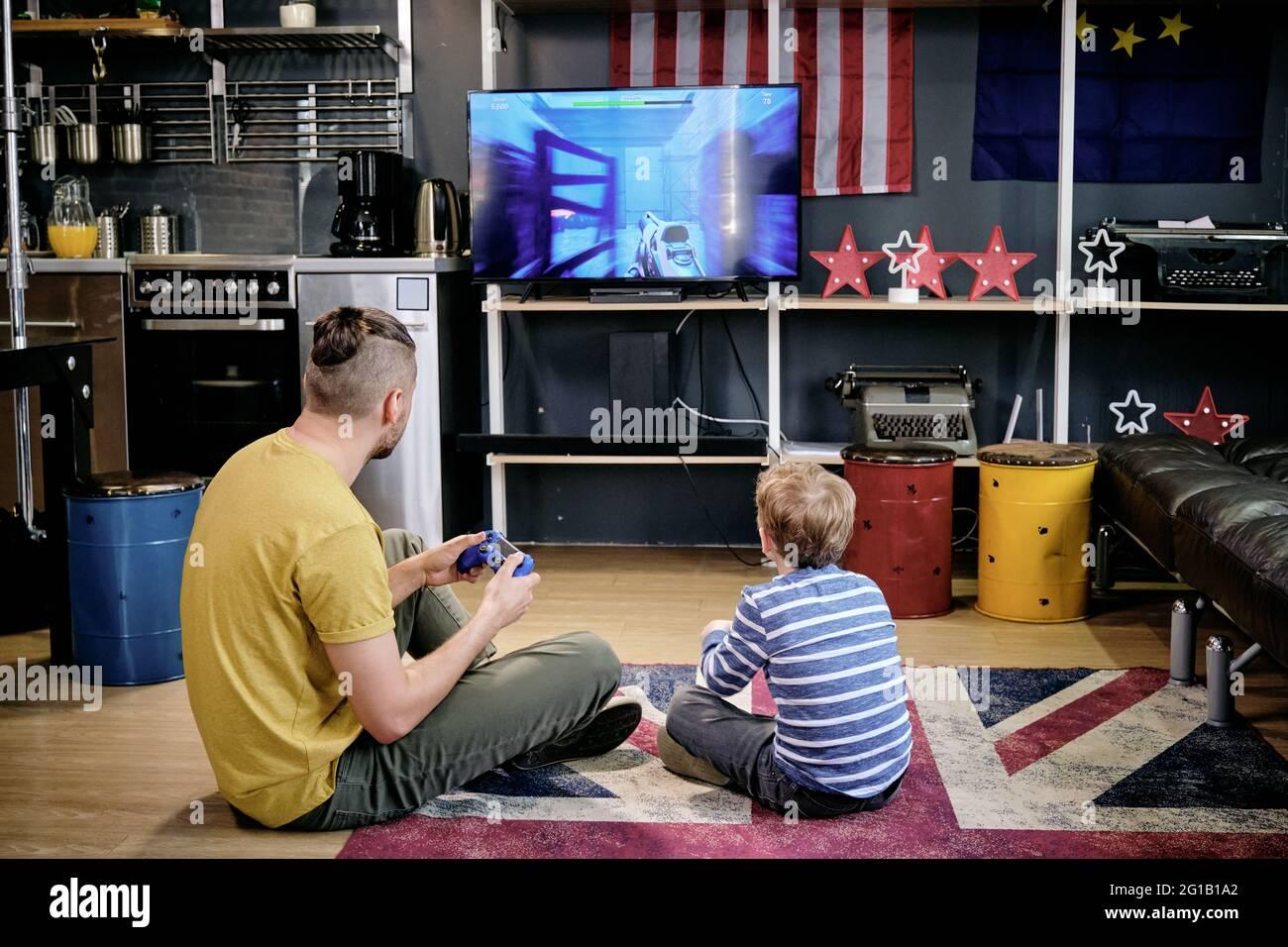 Vista posterior de un joven y un niño jugando a videojuegos en el suelo Foto de stock