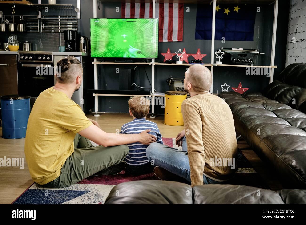 Vista trasera de la familia de tres jugando a videojuegos en la sala de estar Foto de stock