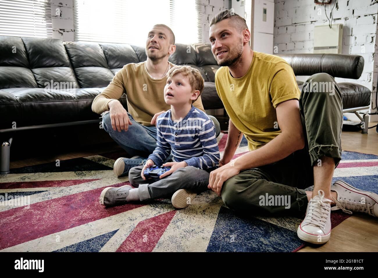Un chico lindo y dos chicos viendo la televisión mientras estaba sentado en el suelo Foto de stock