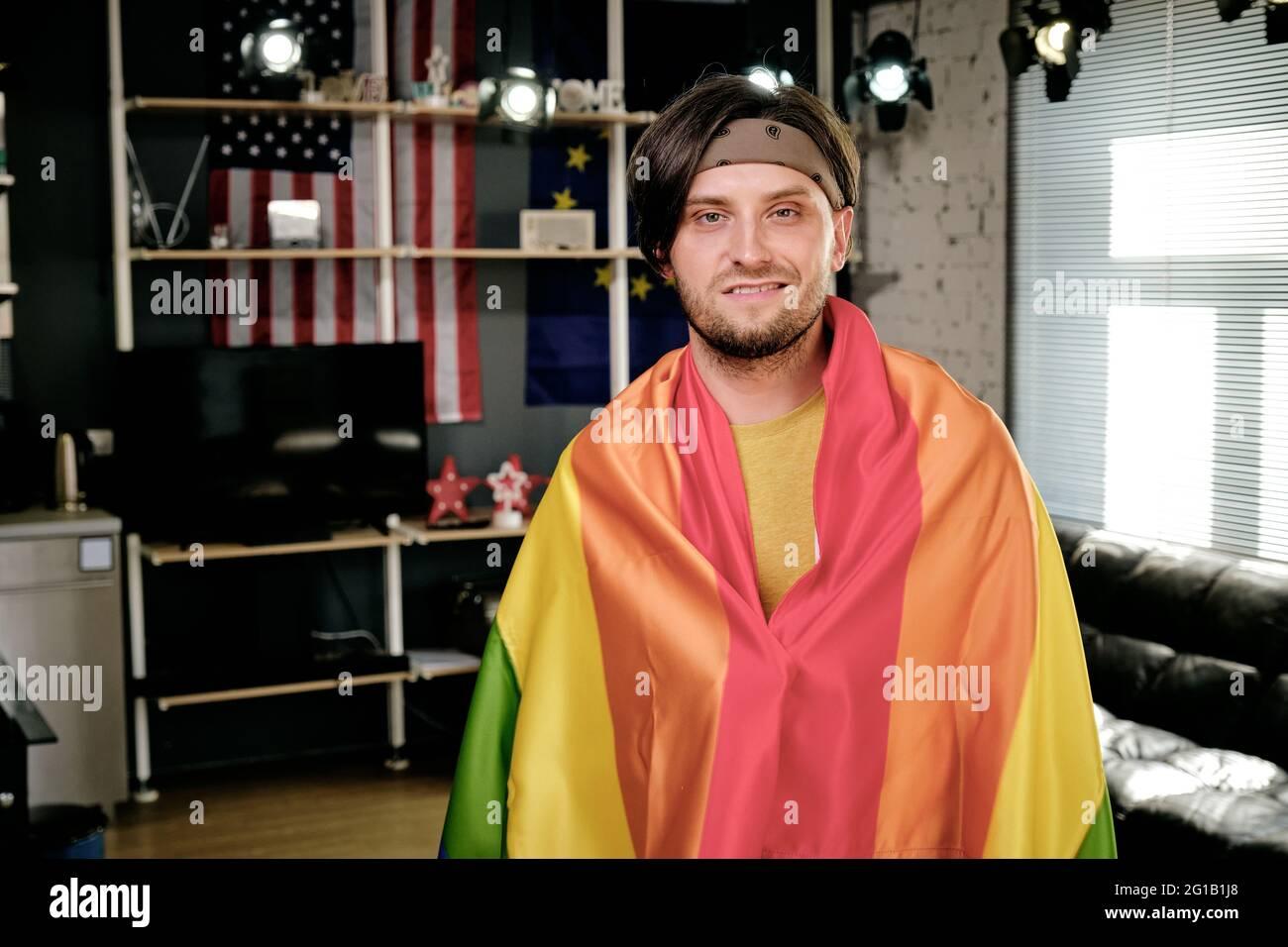 Hombre joven feliz envuelto en una bandera de orgullo de pie en el salón Foto de stock