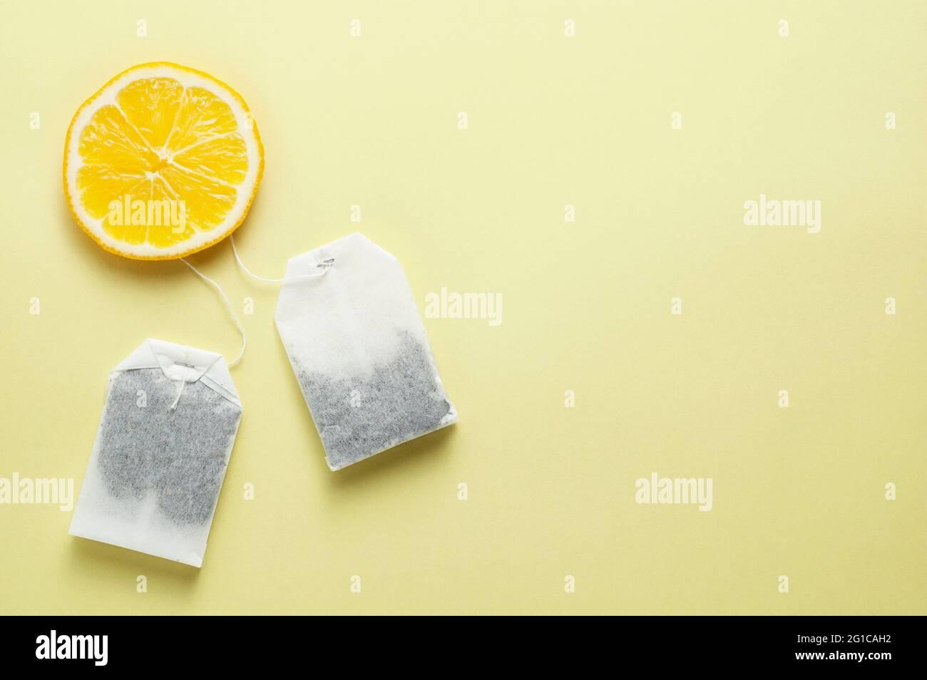 Bolsas de té y una rodaja de limón sobre fondo amarillo Foto de stock