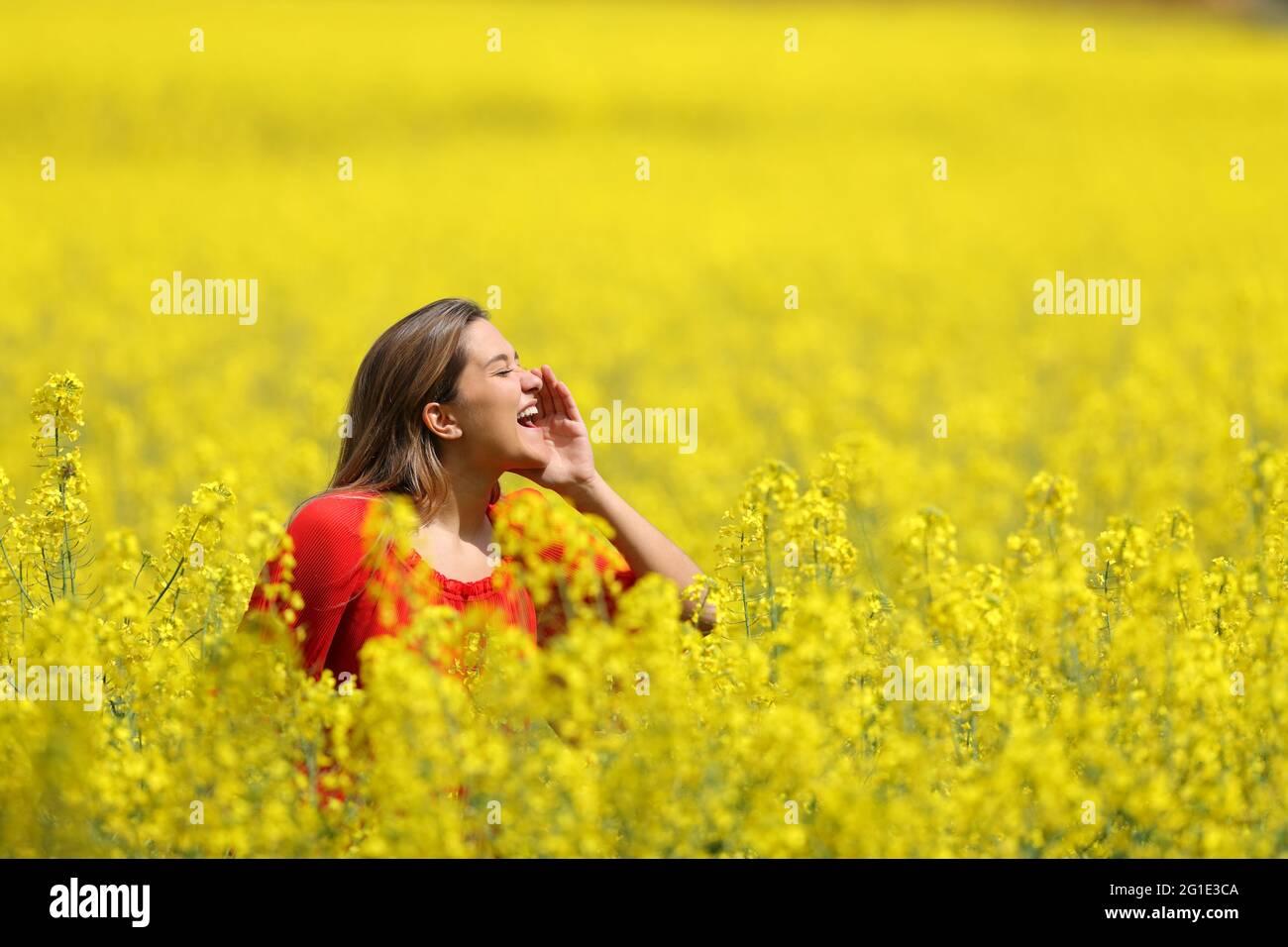 Vista lateral retrato de una mujer feliz en rojo gritando en un campo amarillo en la temporada de primavera Foto de stock
