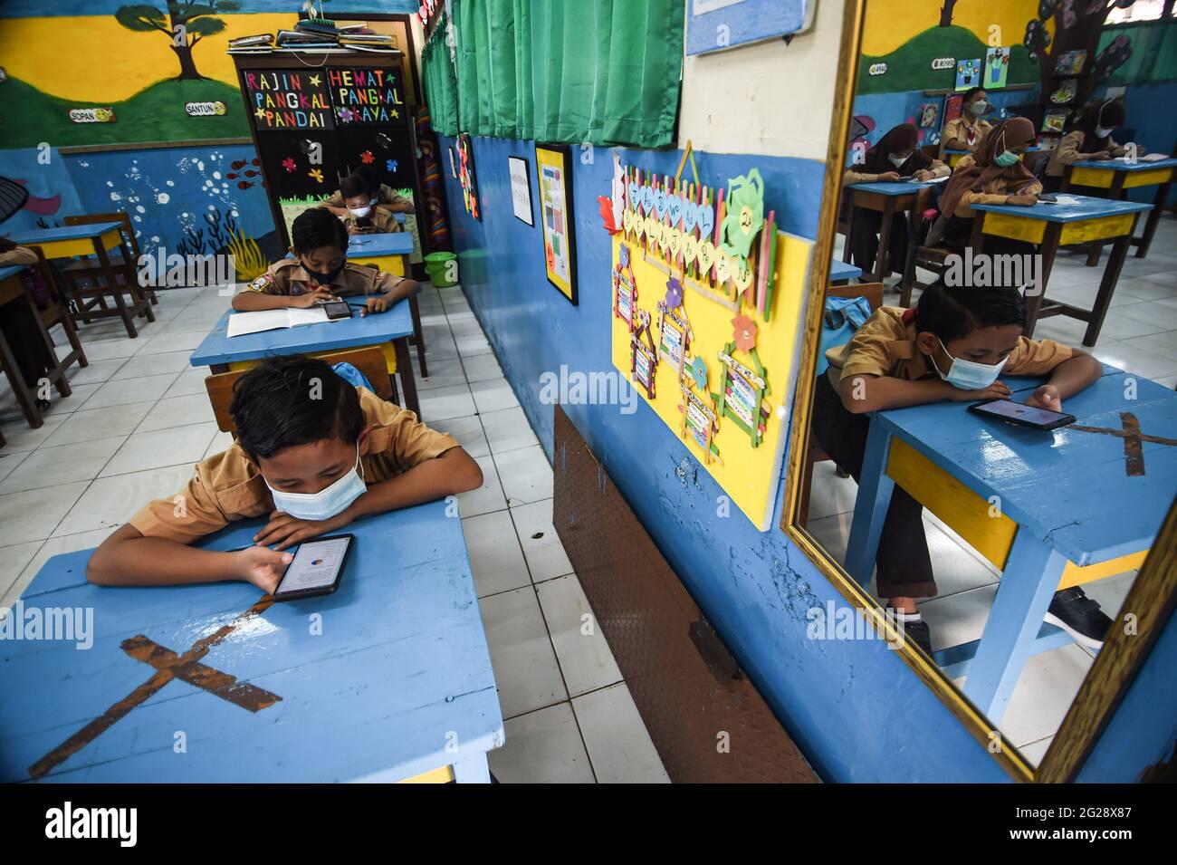 Yakarta, Indonesia. 9th de junio de 2021. Los estudiantes de primaria que usan máscaras faciales son vistos en un salón de clase durante una actividad de aprendizaje cara a cara de prueba en medio del brote de COVID-19 en una escuela en Yakarta, Indonesia, el 9 de junio de 2021. Crédito: Agung Kuncahya B./Xinhua/Alamy Live News Foto de stock