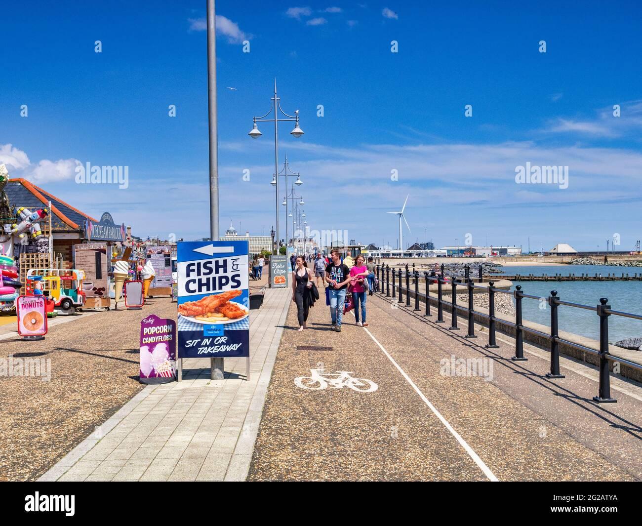 15 de junio de 2019: Lowestoft, Suffolk, Reino Unido - Pareja joven paseando por el paseo marítimo en un soleado día de verano en la costa, signo de pescado y patatas fritas. Foto de stock