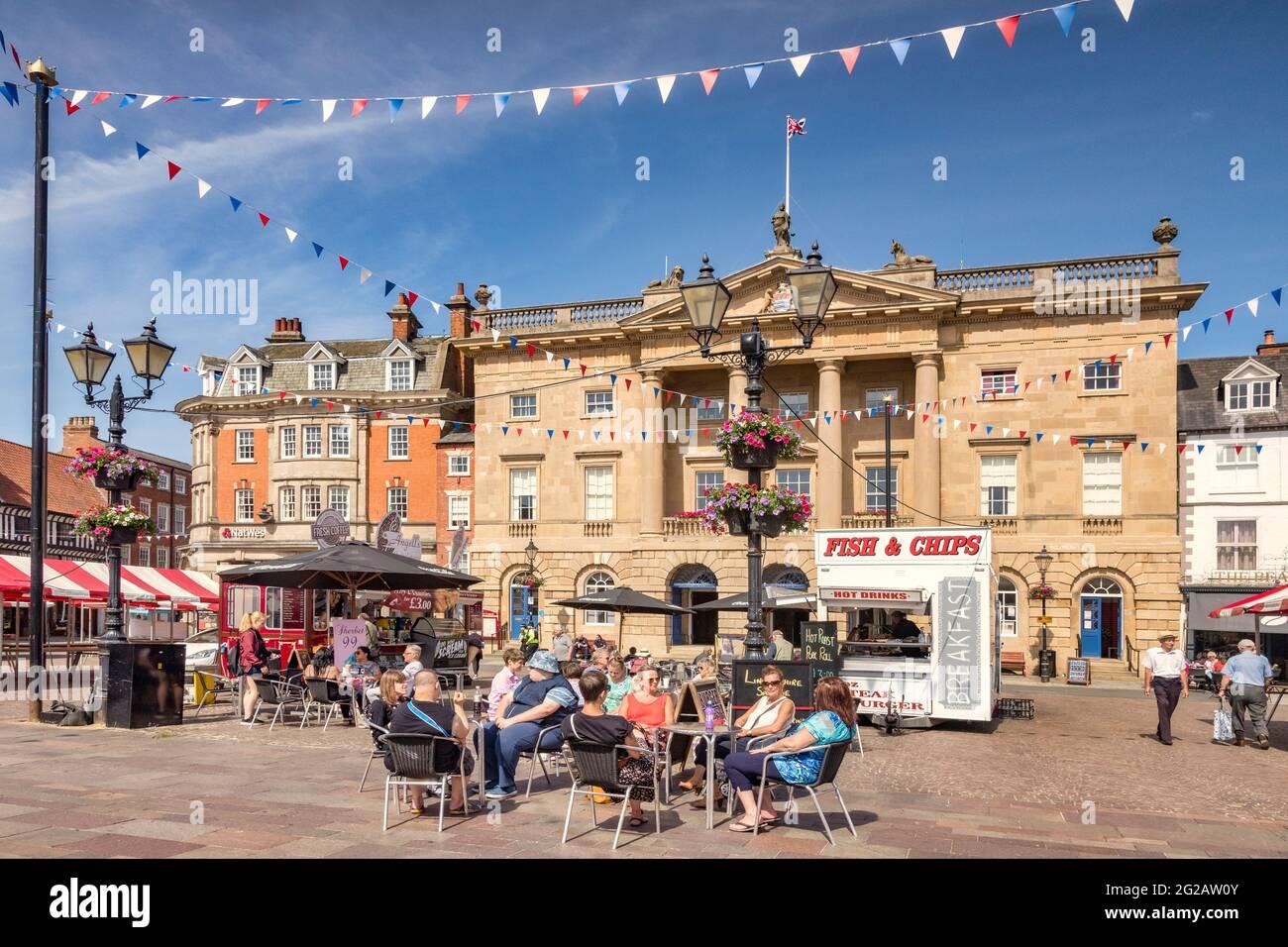 4 de julio de 2019: Newark on Trent, Nottinghamshire, Reino Unido - Gente bebiendo café en un café en la histórica plaza del mercado, con el Ayuntamiento detrás. Foto de stock