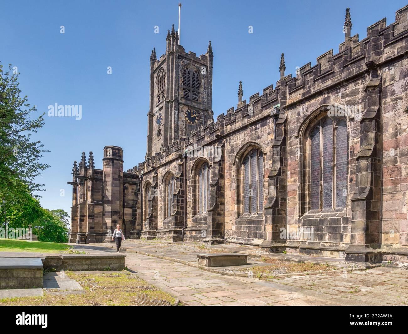12 de julio de 2020: Lancaster, Reino Unido - La Iglesia del Priorato de Santa María en verano, la mujer caminando. Foto de stock