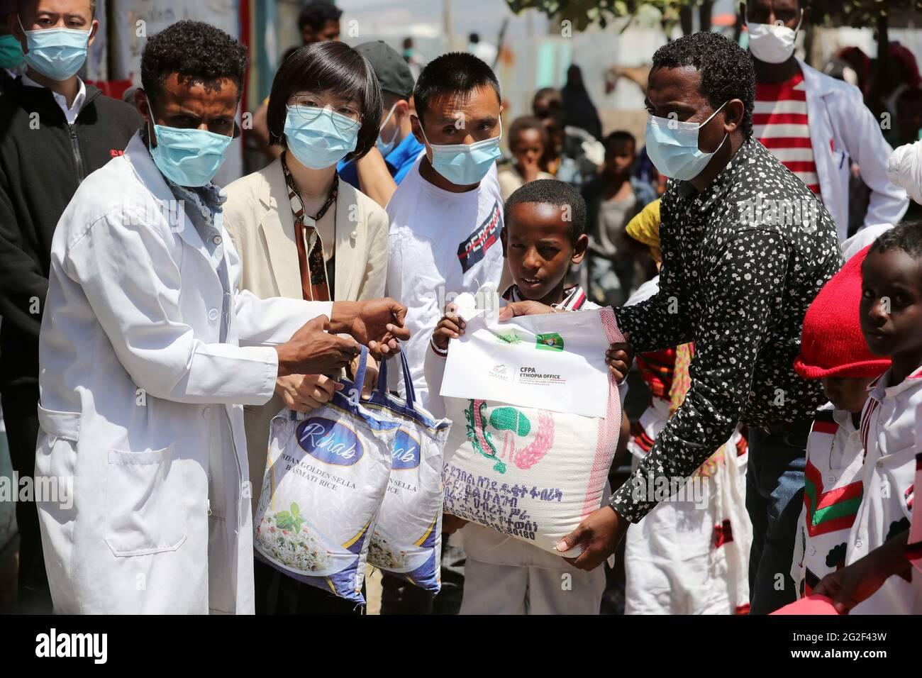 Dukem, Escuela Primaria Obaay, en la ciudad de Dukem, en el estado regional de Oromia en Etiopía. 9th de junio de 2021. Huang Xiaocen (2nd L, front), subdirector de la Fundación China para el Alivio de la Pobreza (CFPA) Etiopía, distribuye alimentos a estudiantes locales en la Escuela Primaria Obaay, en la ciudad de Dukem, en el estado regional de Oromia, Etiopía, el 9 de junio de 2021. CFPA distribuyó el miércoles paquetes de alimentos a más de 400 estudiantes en la Escuela Primaria Obaay, en la ciudad de Dukem, en el estado regional de Oromia, Etiopía. Crédito: Wang Ping/Xinhua/Alamy Live News Foto de stock