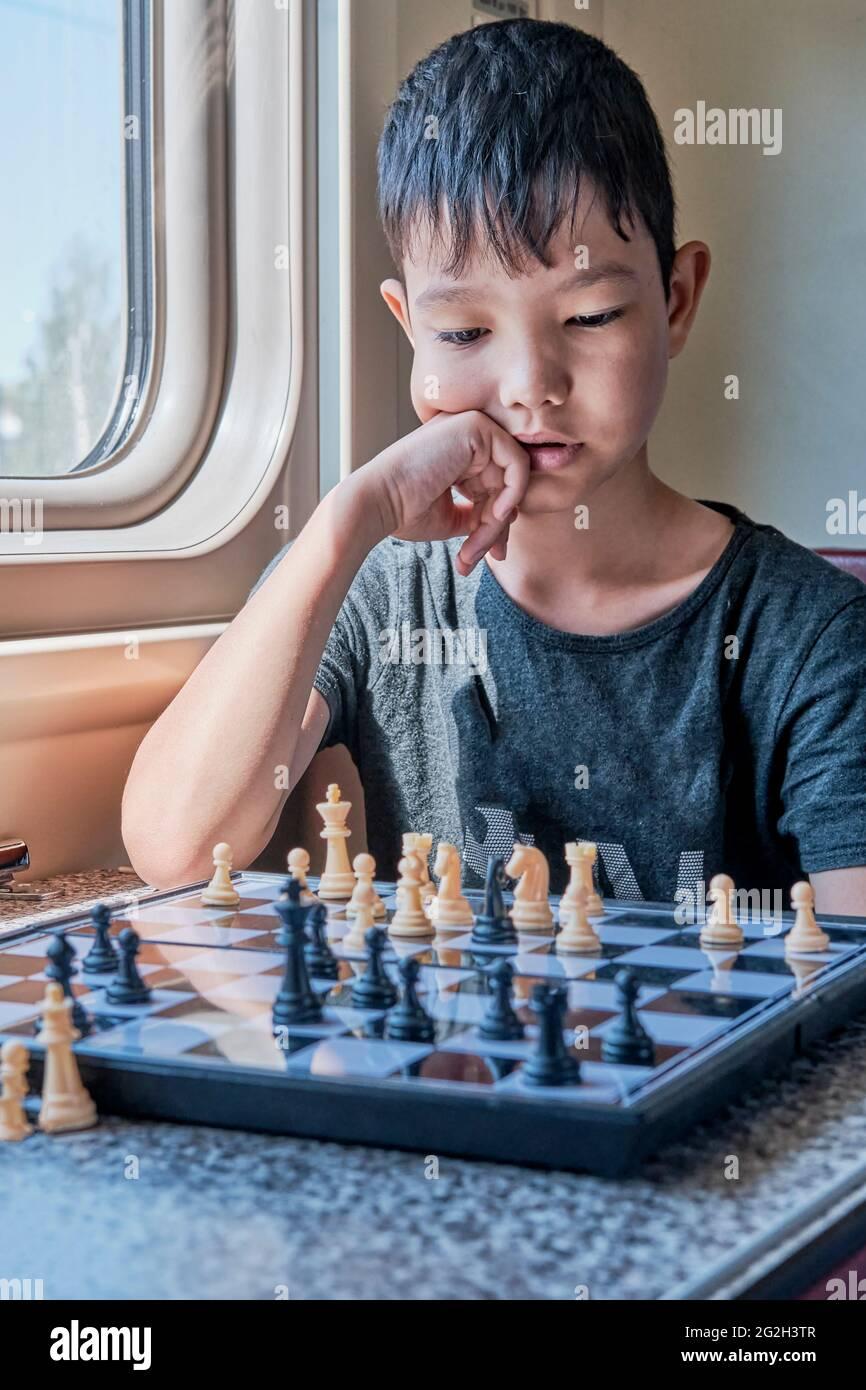 Niño asiático ponderando un movimiento en un juego de ajedrez sentado en el tren Foto de stock