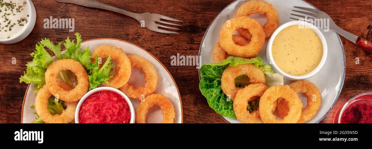 Panorama de los anillos de calamares. Anillos de calamar con vino y varias salsas, la parte superior plana rodó sobre una mesa de madera rústica oscura Foto de stock