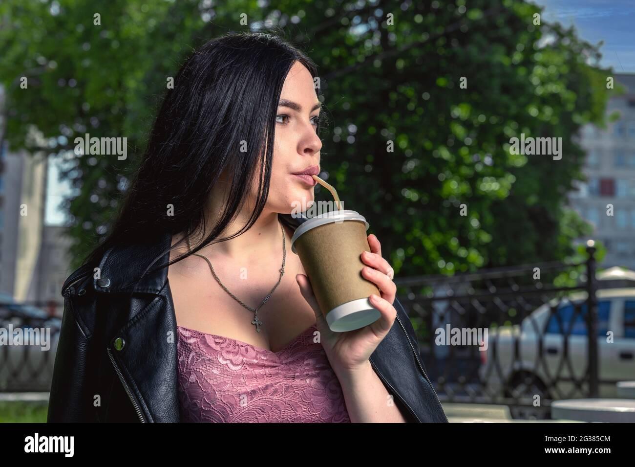 Mujer joven tomando café en la calle. Mujer en la calle de la ciudad bebiendo una bebida caliente. Imagen de una mujer joven atractiva que bebe café en la t Foto de stock