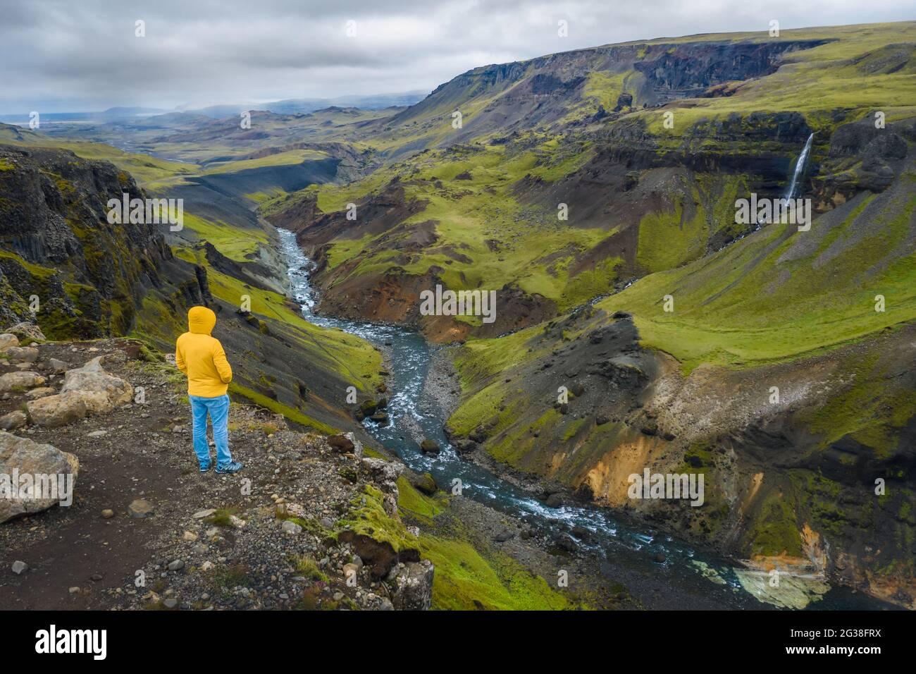 Vista aérea del hombre disfrutando del paisaje de Islandia del valle de las tierras altas y el río Fossa con el arroyo de agua azul y colinas verdes y acantilados cubiertos de musgo. Foto de stock