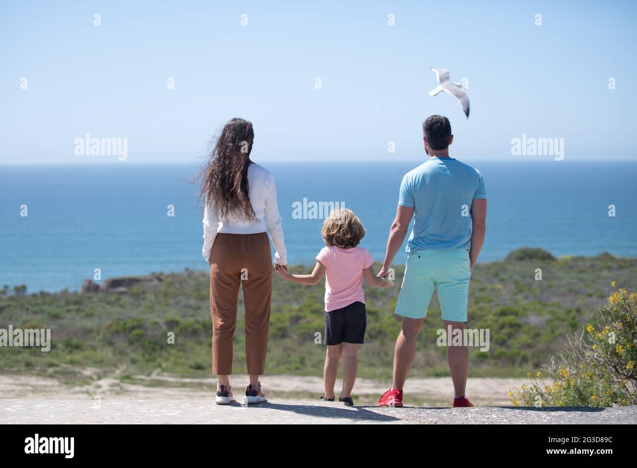 Padre, madre y niño en la playa de verano al atardecer en Hawai. Concepto de familia amigable. Foto de stock